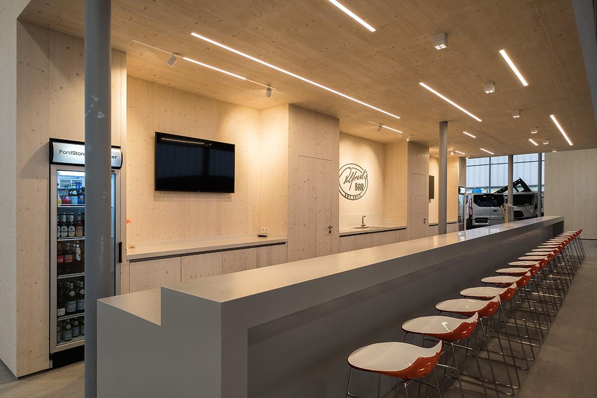Tischlerarbeiten und Einbauschränke in Autohaus in Halle Westf., Theke aus Mineralwerkstoff, grifflose Fronten aus Fichtenholz-Dreischichtplatte